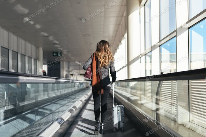 Unrecognizable woman walking with suitcase in the airport.