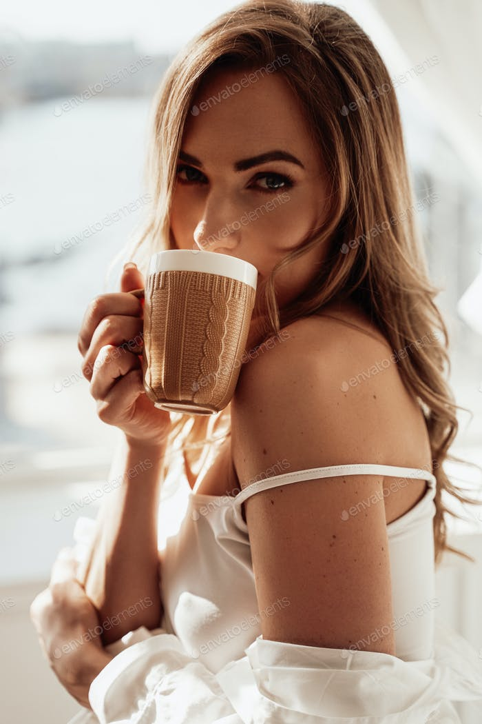 Graceful young woman in lingerie posing with a cup of coffee over the white background