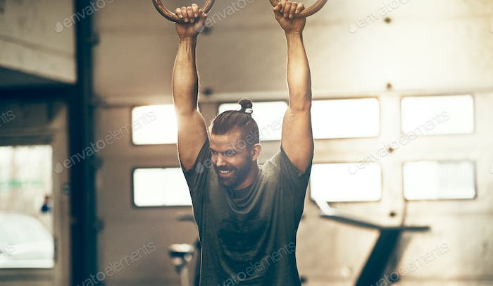 Fit young man working out on rings in a gym