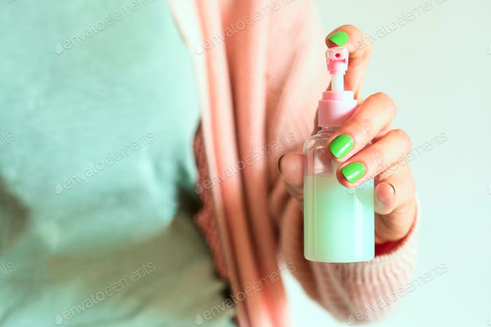 Pink lotion doser in feamle hand. Pastel colors