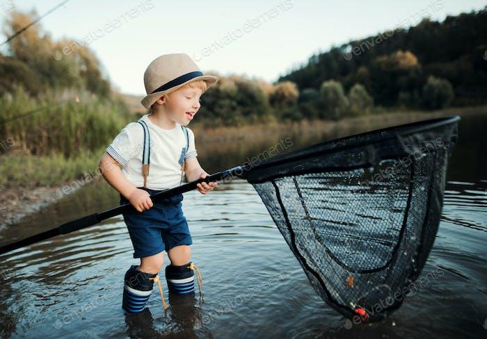 Un niño pequeño de pie en el agua y sosteniendo una red junto a un lago, la pesca.
