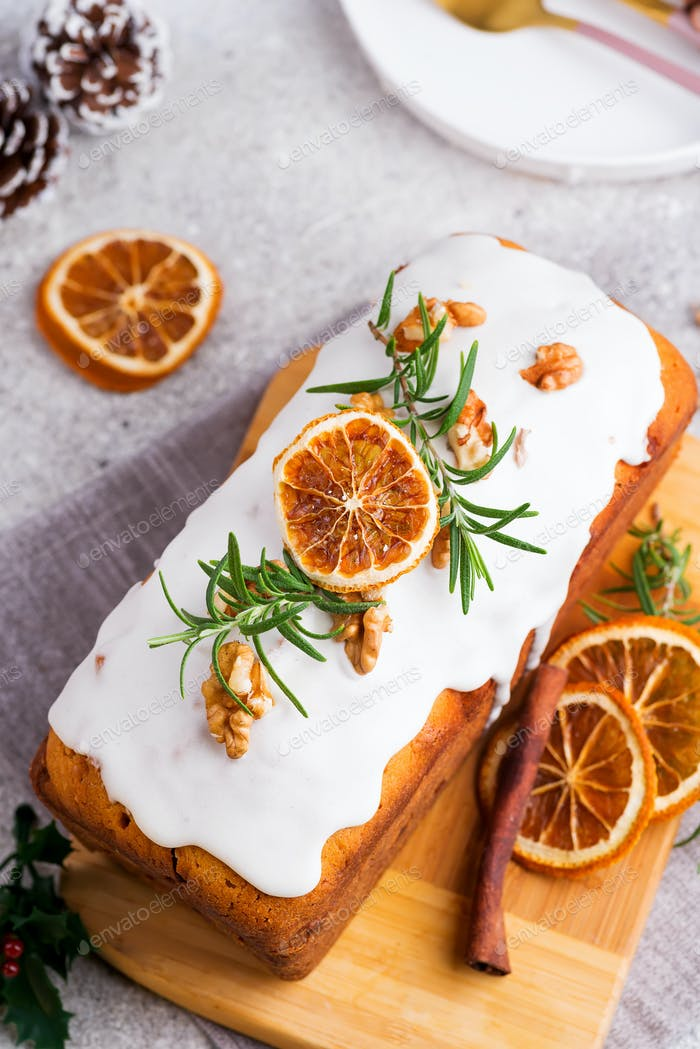 Fruit cake dusted with icing, nuts and dry orange on stone background, flat lay. Christmas and