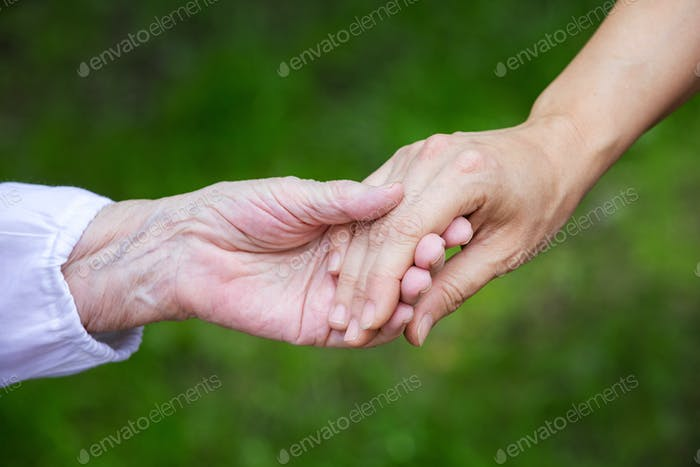 Hands of young adult and senior women over green background