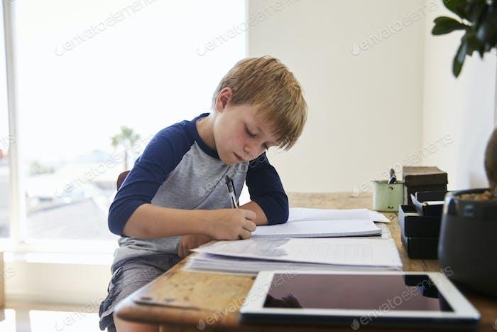 Boy Sits At Desk In Bedroom With Digital Tablet Doing Homework
