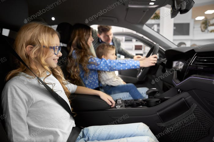 Friendly family testing and observing car in auto salon