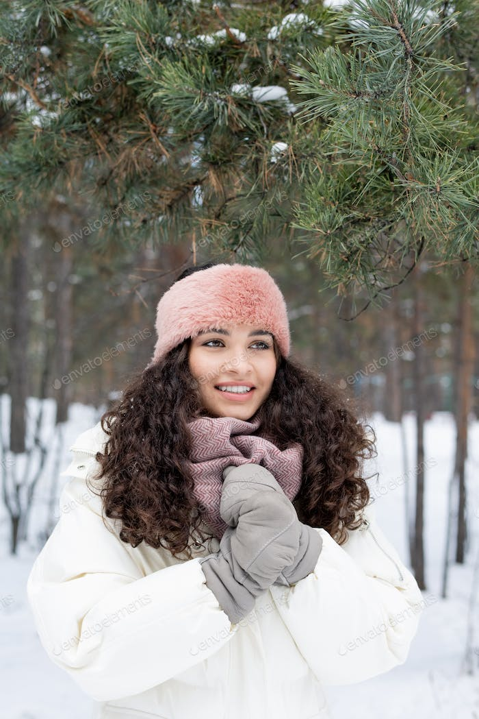 Cute cheerful girl with toothy smile wearing warm winterwear on winter day