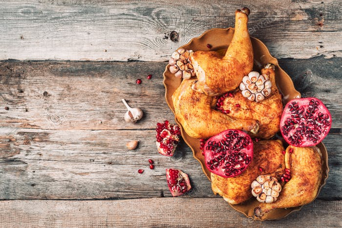 Roasted chicken with pomegranate and garlic on wooden background. Friends or family dinner. Festive