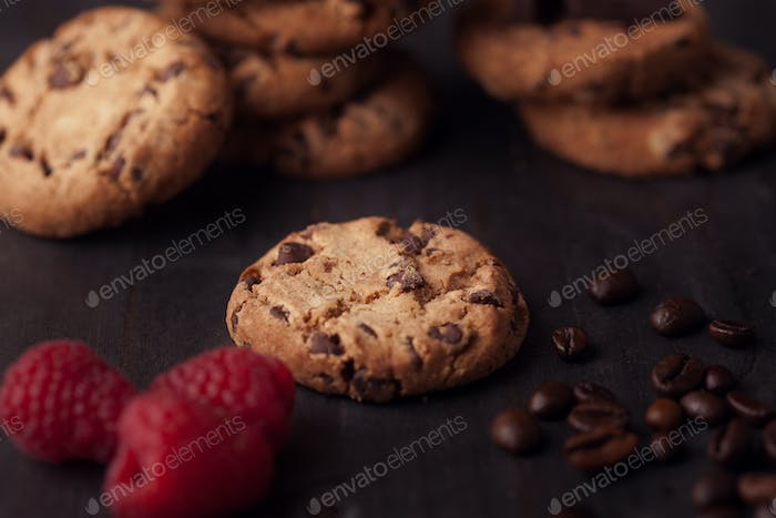 Chocolate chips cookies with red raspberries and coffee beans on dark old wooden table