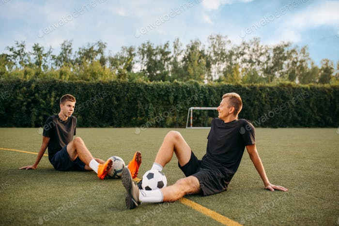 Two male soccer players resting on the grass