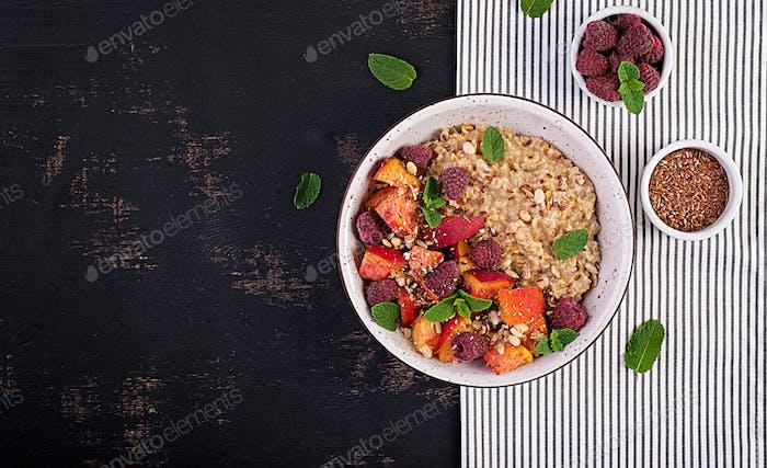 Oatmeal porridge with raspberry and peach on dark background. Healthy breakfast.