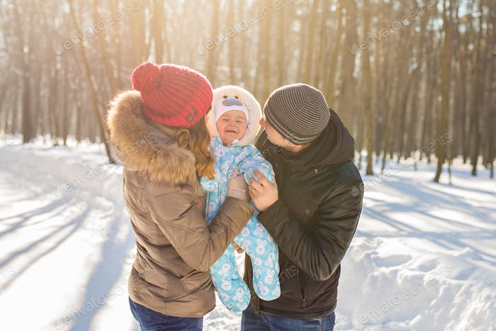 happy young family with their baby son spending time outdoor in the winter park