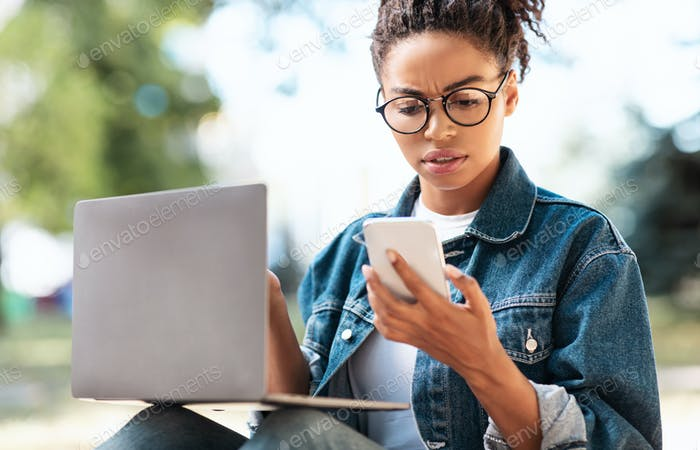 Black Woman Reading Message On Phone Frowning Working Outdoors