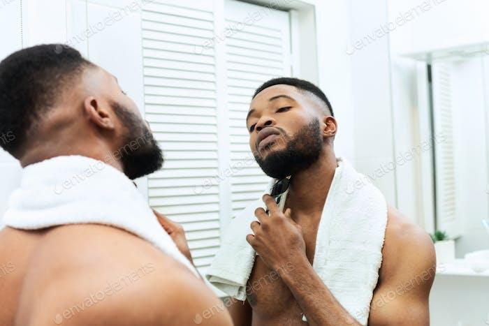 Junger Mann rasiert seinen Bart mit Elektrorasierer, Blick auf Spiegel