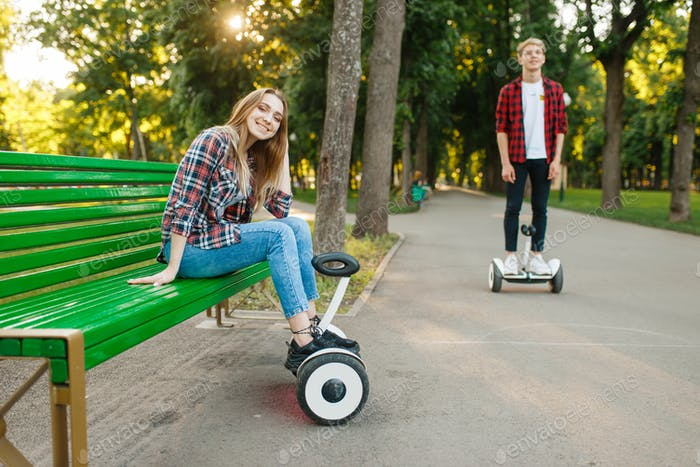 Couple leisures with gyro board in summer park