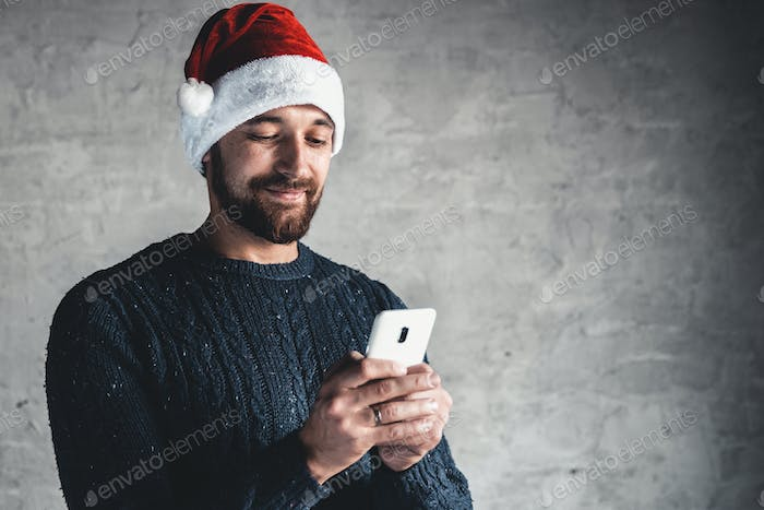 Typing message. Man holding mobile phone while standing against grey background