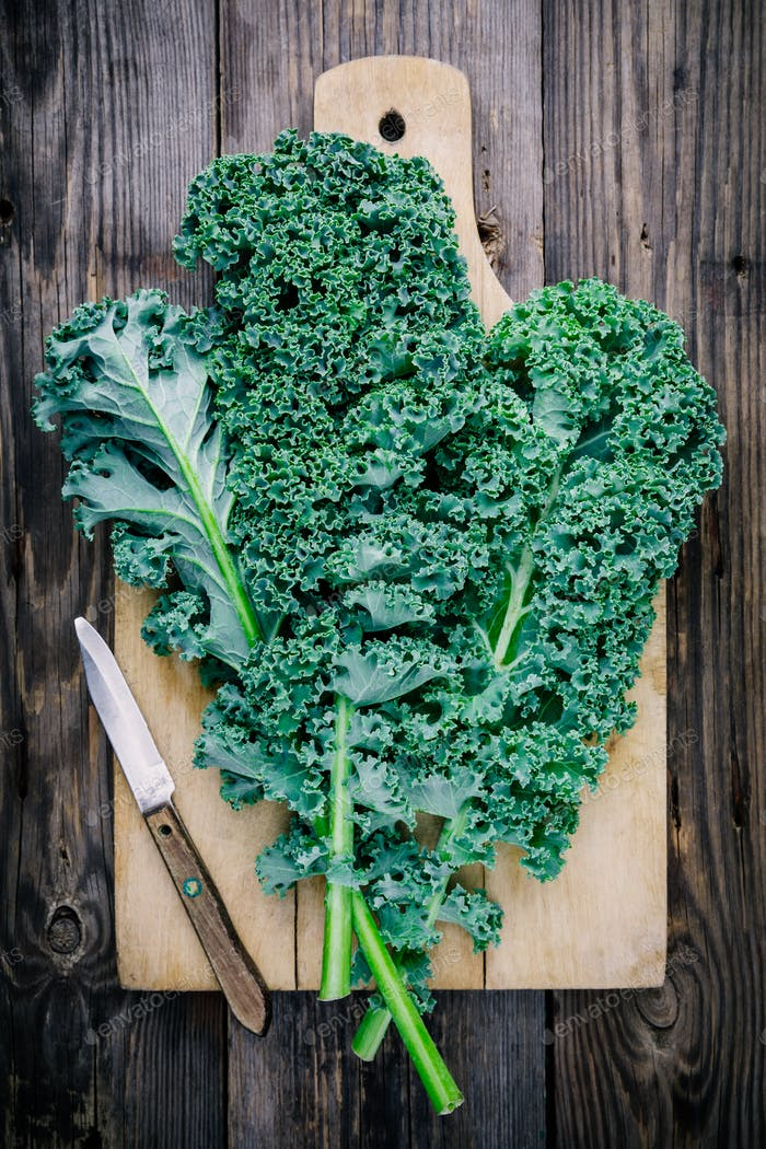 Fresh raw green superfood kale curly cabbage leaves