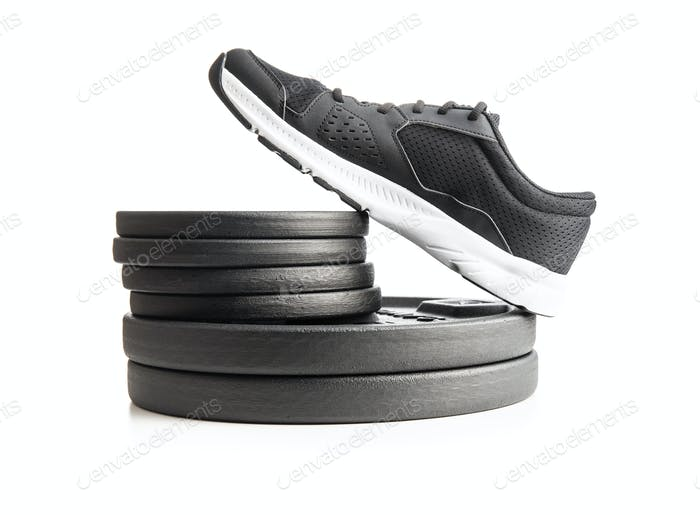 Black sports shoes and weights dumbbells