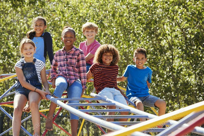 Pre-teen friends sitting on climbing frame in playground