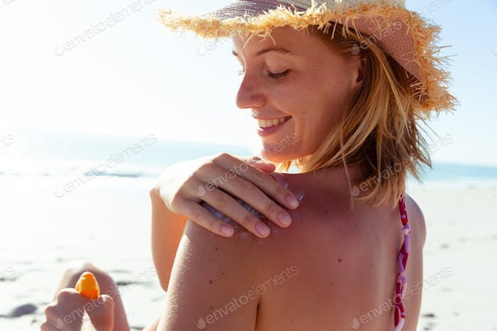 Woman applying sunscreen on her back at the beach