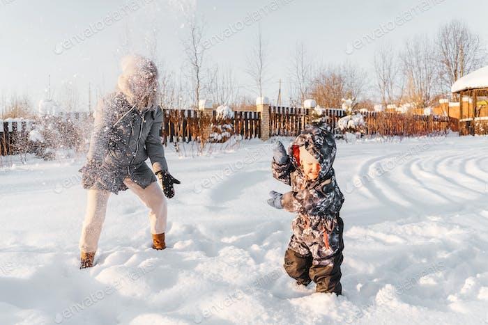 Madre feliz y el niño arrojan nieve, sonriendo