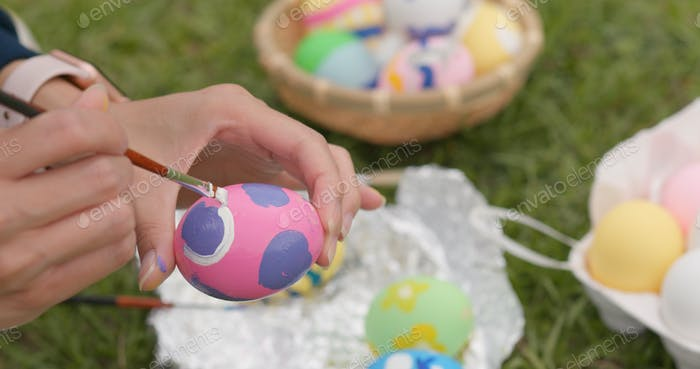 Woman drawing Easter egg on green grass