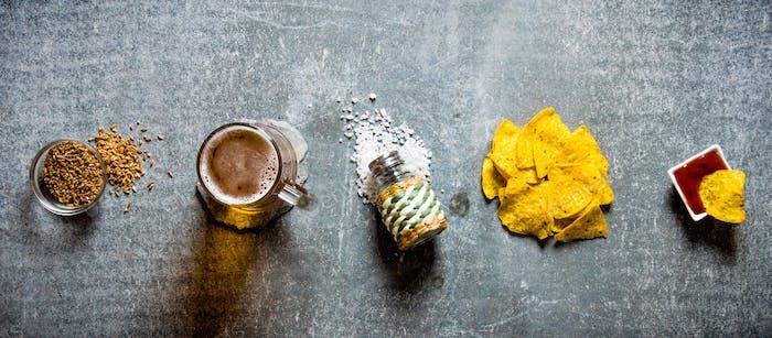 Cerveza ambientada en superficie de piedra vieja. En el set: cerveza, papas fritas, sal, lúpulo y malta.