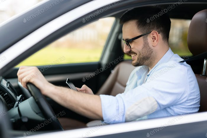 Businessman ignoring safety and texting onmobile phone while driving