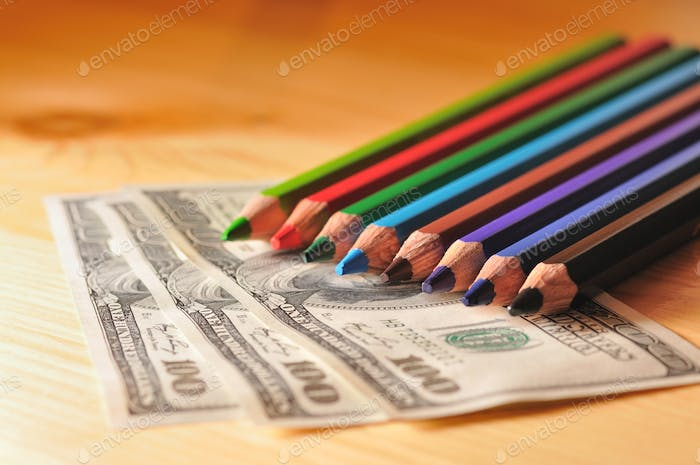 Photo of multi-colored pencils on the dollar bill