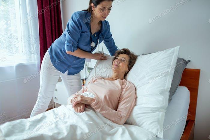Home Nurse Making Elderly Patient Bed.