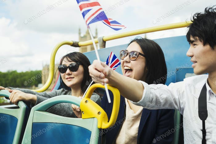 Three tourists waving Union Jack flags on a tour bus
