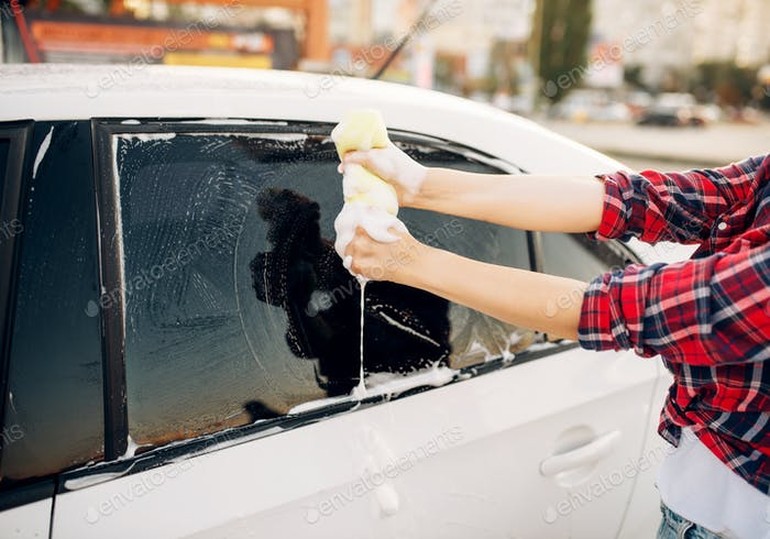 Female person scrubbing vehicle window with foam