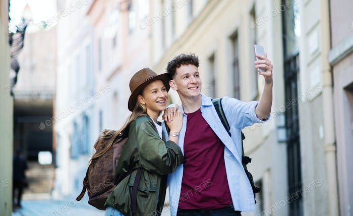 Young couple travelers with smartphone sightseeing in city on holiday, taking selfie