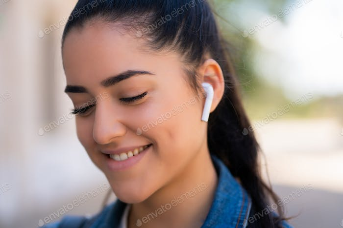 Woman listening to music with earpods.