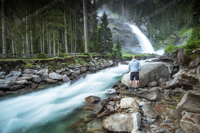 Man standing at Krimml Waterfalls in High Tauern National Park A