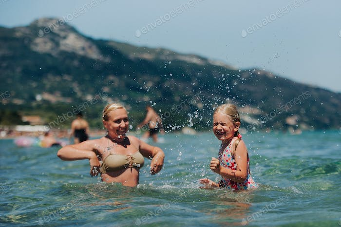 mother with daughter plays in the water, beautiful swimwear, laughs and smiles, splashes of water