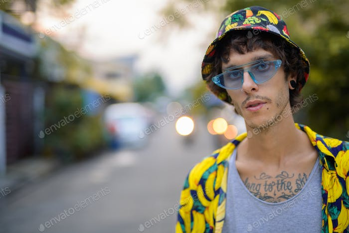 Face of young rebellious man with eccentric fashion outdoors