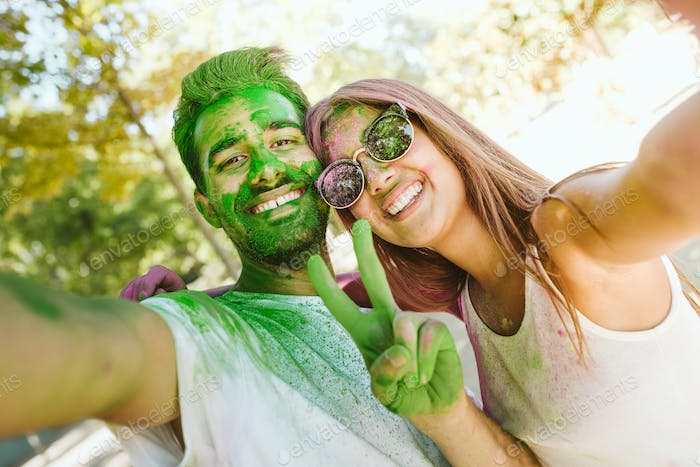 Beautiful young couple playing in the park on holi colours festi