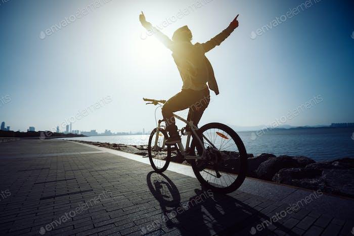 happy woman riding mountain bike on seaside trail during sunrise