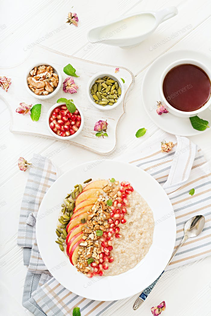 Tasty and healthy oatmeal porridge with apples, pomegranate and nuts