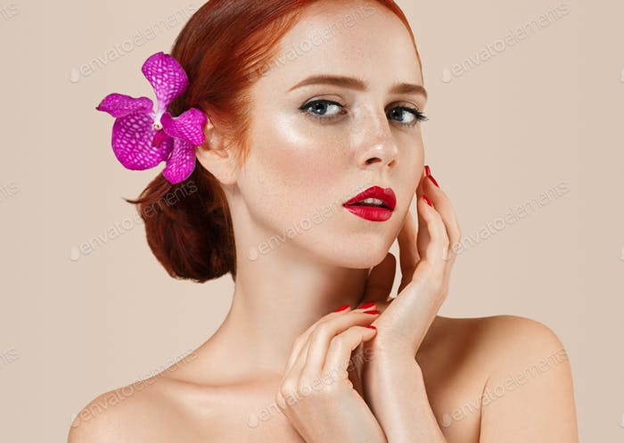 Beautiful woman portrait with flower in hair. manicure red lips and nails white background