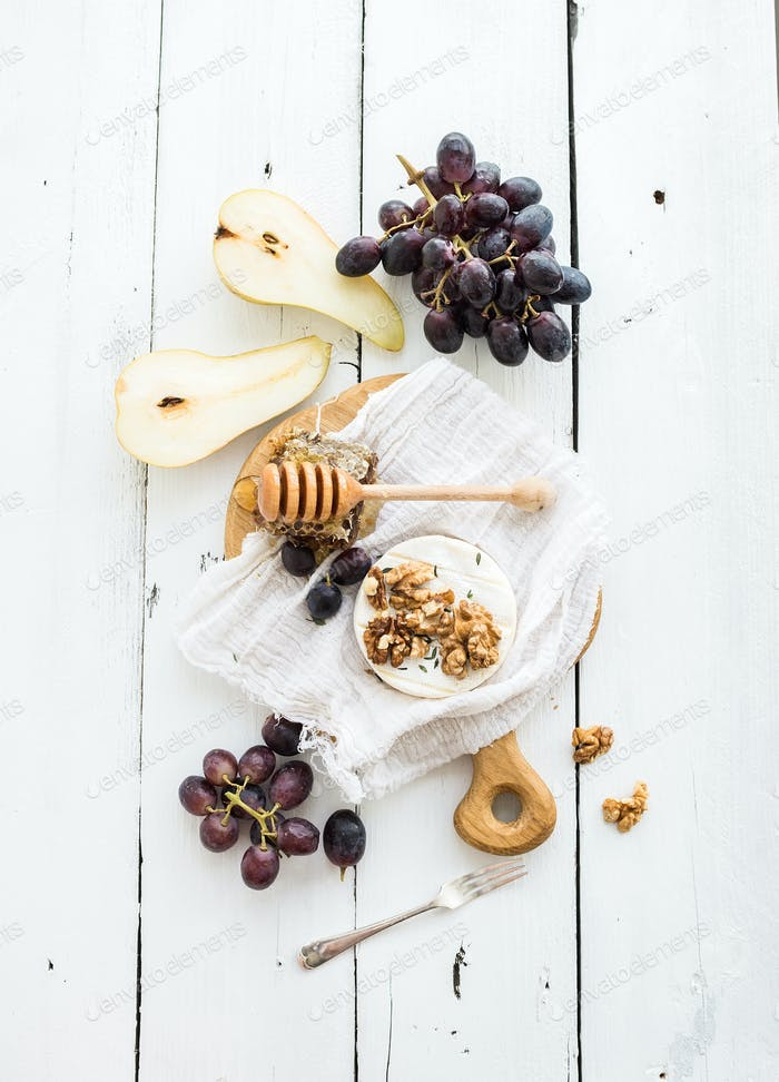Camembert-Käse mit Trauben, Walnüssen, Birne und Honig auf Vintage-Metallplatte