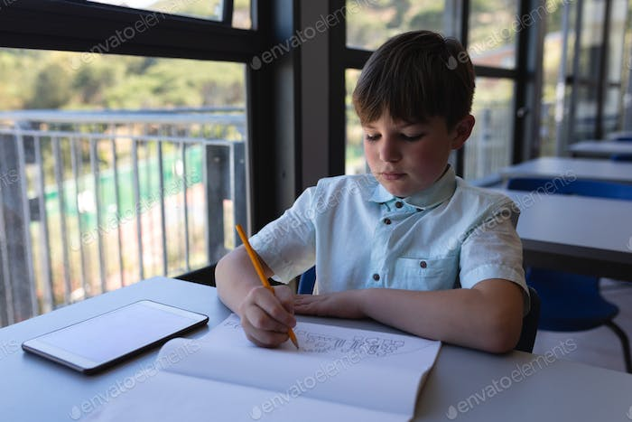 Front view of schoolboy drawing on notebook at desk in classroom of elementary school