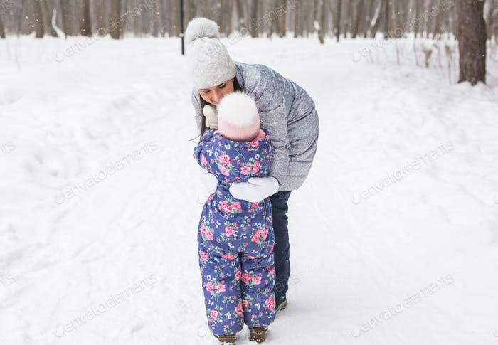 Winter, family and childhood concept - mother is walking with her little daughter in snowy forest