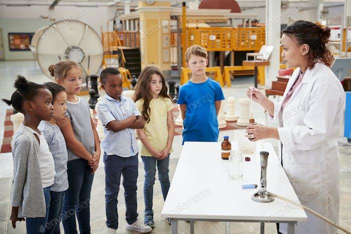Labortechniker mit Gruppe von Kindern, die ein Experiment durchführen