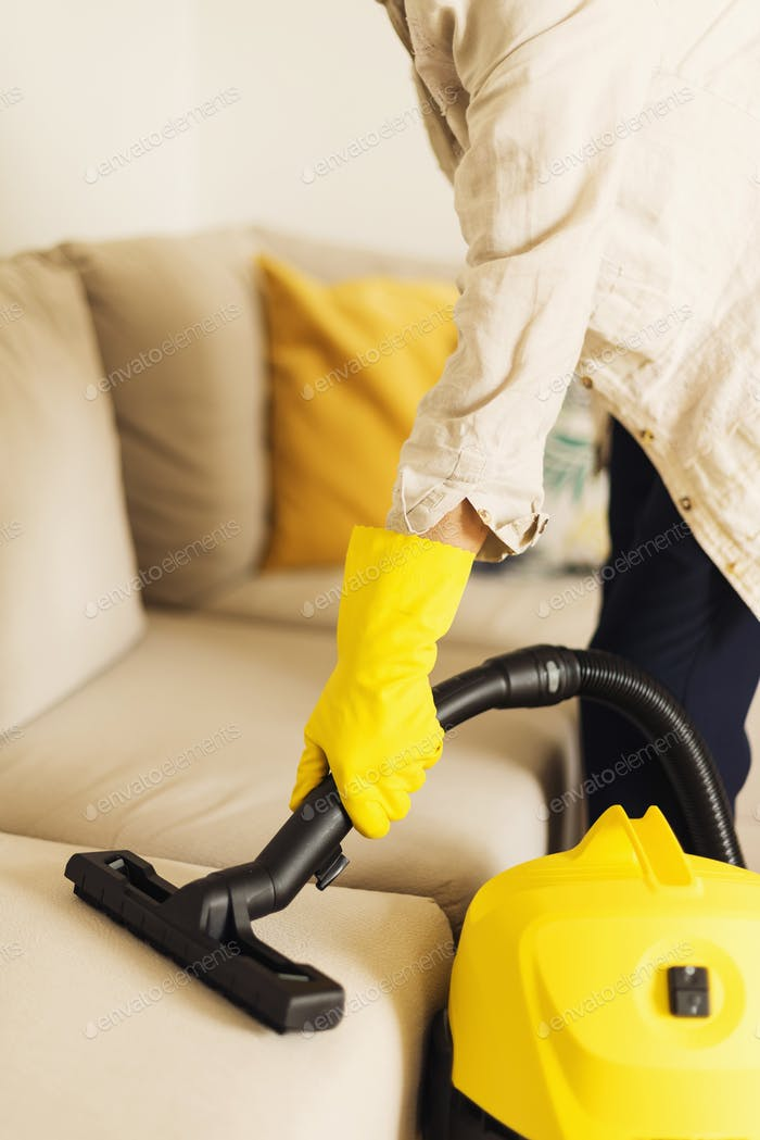 Woman cleaning sofa with yellow vacuum cleaner. Copy space. Clean concept