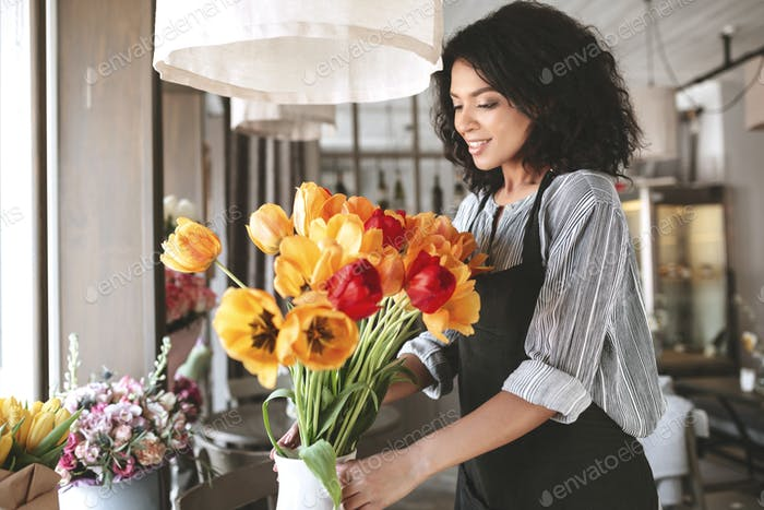 Pretty African American girl with dark curly hair working with flowers
