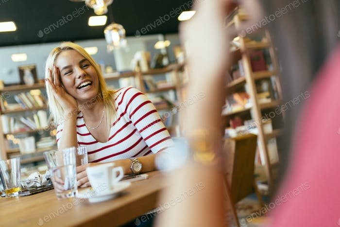 Friends gossiping and chatting in cafe