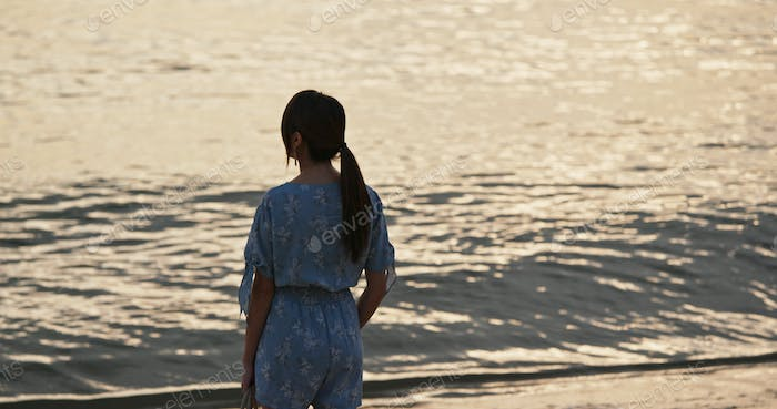 Woman stand on the beach and enjoy the view of the sea at sunset time