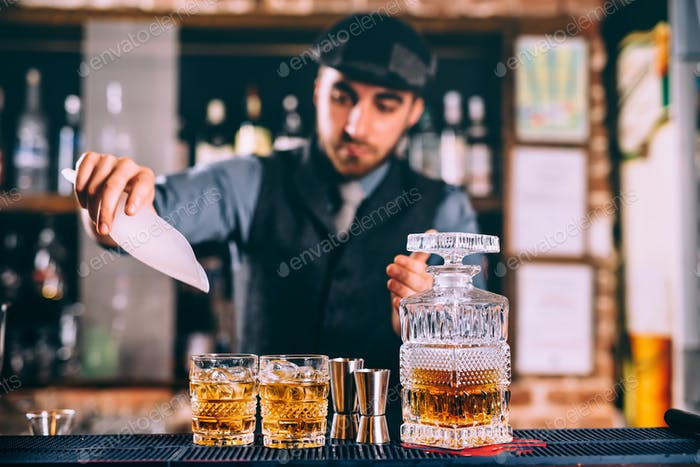 close up of elengant bartender pouring whiskey and ice on fresh cocktails in modern bar