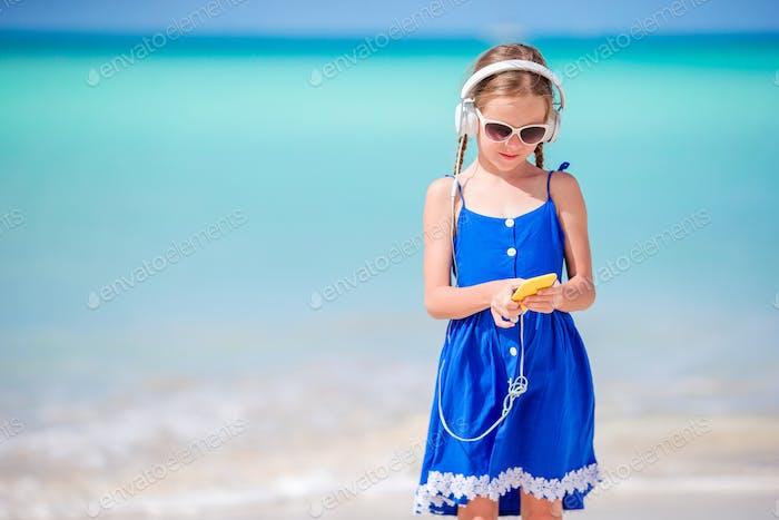 Kleine entzückende Mädchen hören Musik Hintergrund Meer sitzen auf dem Sand